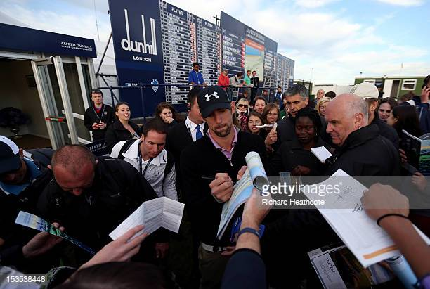 Michael Phelps signs autographs for spectators after finishing his round during the third round of The Alfred Dunhill Links Championship at The Old...