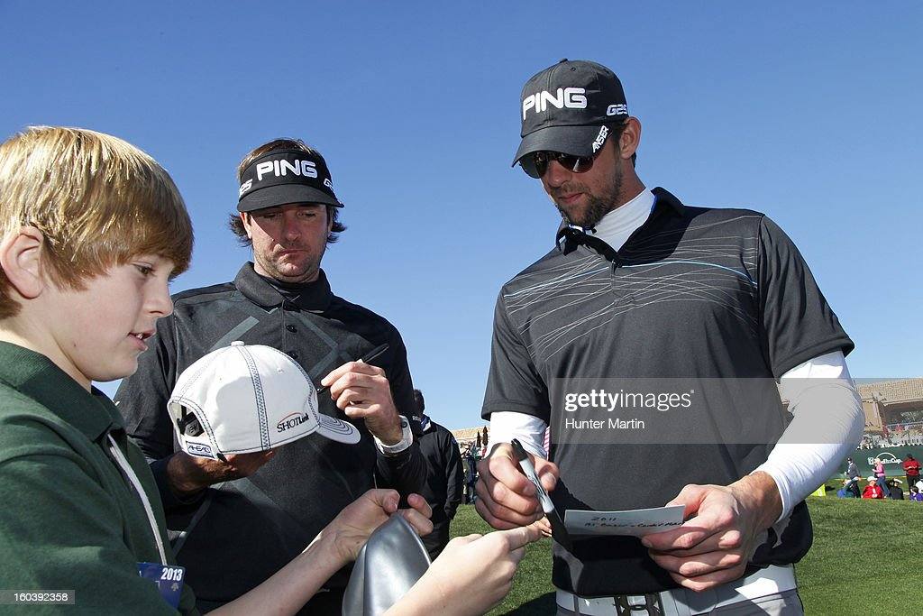 Michael Phelps signs autographs with Bubba Watson on the 18th green during the Wednesday Pro-Am of the Waste Management Phoenix Open at TPC Scottsdale on January 30, 2013 in Scottsdale, Arizona.