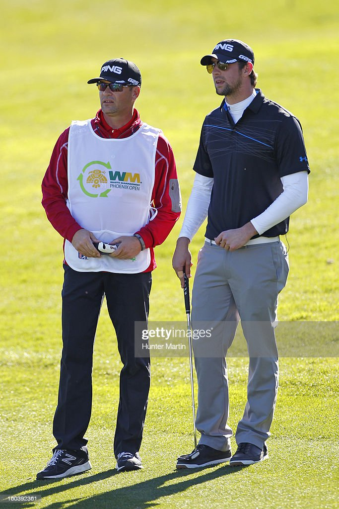 Michael Phelps stands with his caddie on the 18th green during the Wednesday Pro-Am of the Waste Management Phoenix Open at TPC Scottsdale on January 30, 2013 in Scottsdale, Arizona.