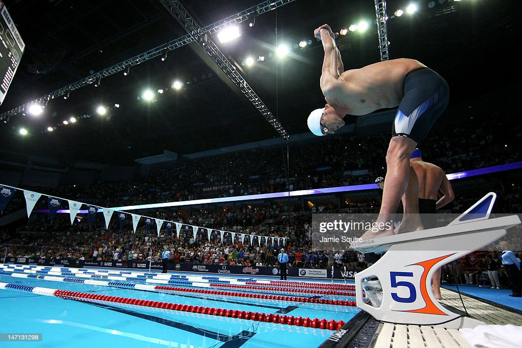 Michael Phelps stretches on the block prior to the start of the championship final heat of the Men's 400 m Individual Medely during the 2012 US...