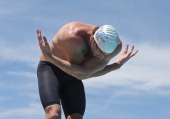 Michael Phelps warms up on the starting block before competing in the Men's 50m Freestyle prelim during day two of the Arena Grand Prix at the...