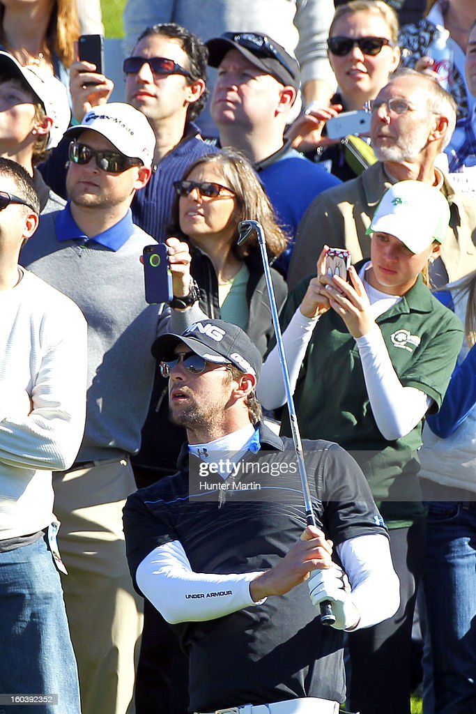 Michael Phelps watches his second shot on the 18th hole during the Wednesday Pro-Am of the Waste Management Phoenix Open at TPC Scottsdale on January 30, 2013 in Scottsdale, Arizona.