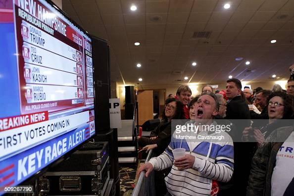 Michael Powlowsky of Hudson cheers as a television screen shows early poll numbers favoring republican presidential candidate Donald Trump at Trump's...