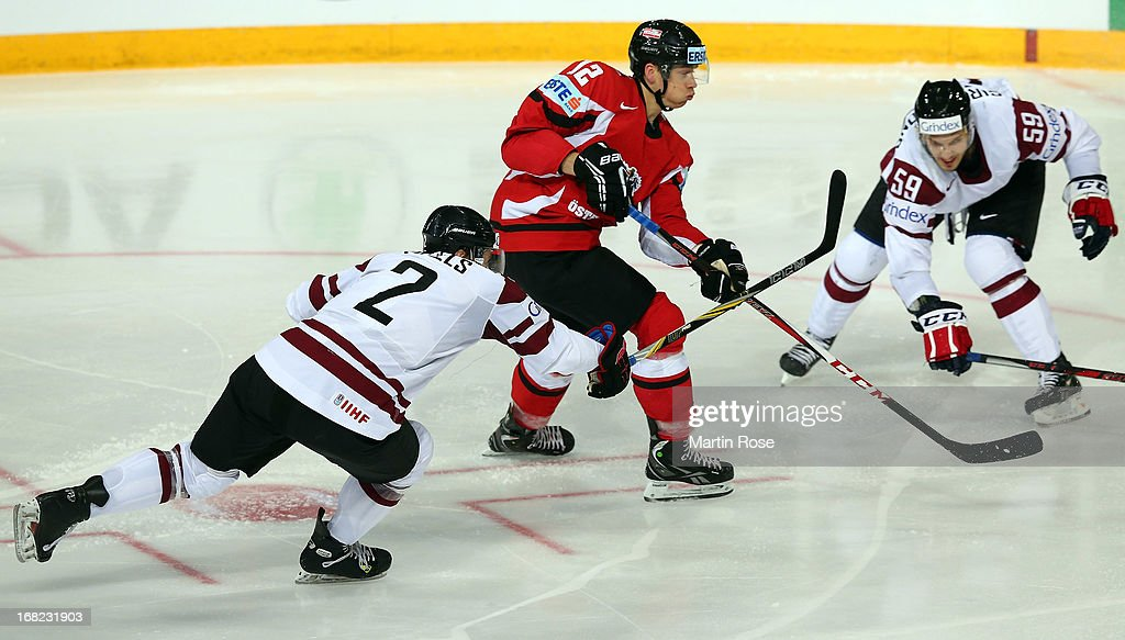 Michael Raffl (#12) of Austria and Agris Saviels (#2) of Latvia battle for the puck during the IIHF World Championship group H match between Austria and Latvia at Hartwall Areena on May 7, 2013 in Helsinki, Finland.