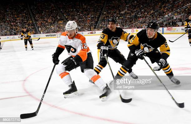 Michael Raffl of the Philadelphia Flyers handles the puck against Conor Sheary of the Pittsburgh Penguins and Brian Dumoulin of the Pittsburgh...