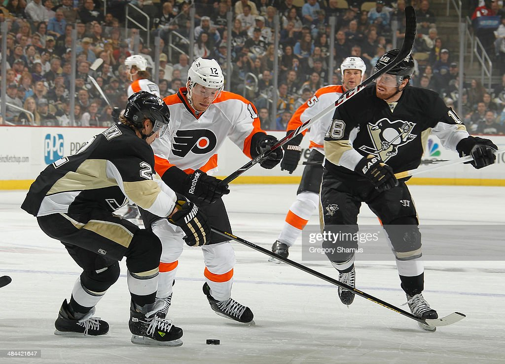 Michael Raffl #12 of the Philadelphia Flyers moves the puck between Matt Niskanen #2 and James Neal #18 of the Pittsburgh Penguins on April 12, 2014 at Consol Energy Center in Pittsburgh, Pennsylvania.