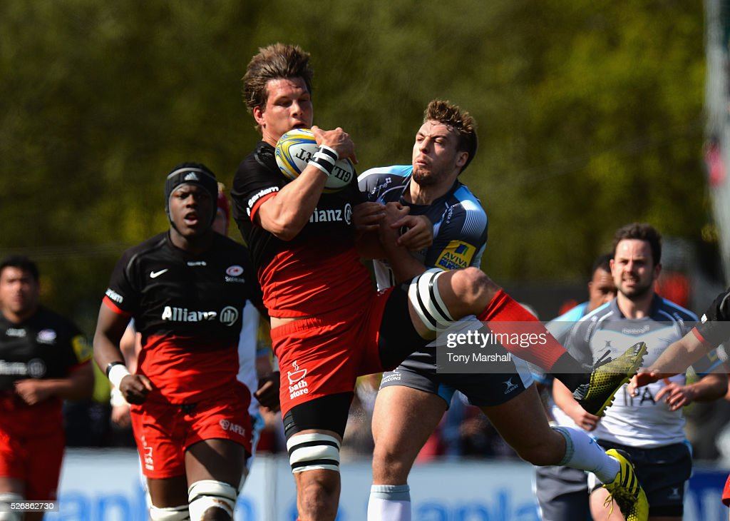 Michael Rhodes of Saracens is tackled by Craig Willis of Newcastle Falcons during the Aviva Premiership match between Saracens and Newcastle Falcons at Allianz Park on May 1, 2016 in Barnet, England.