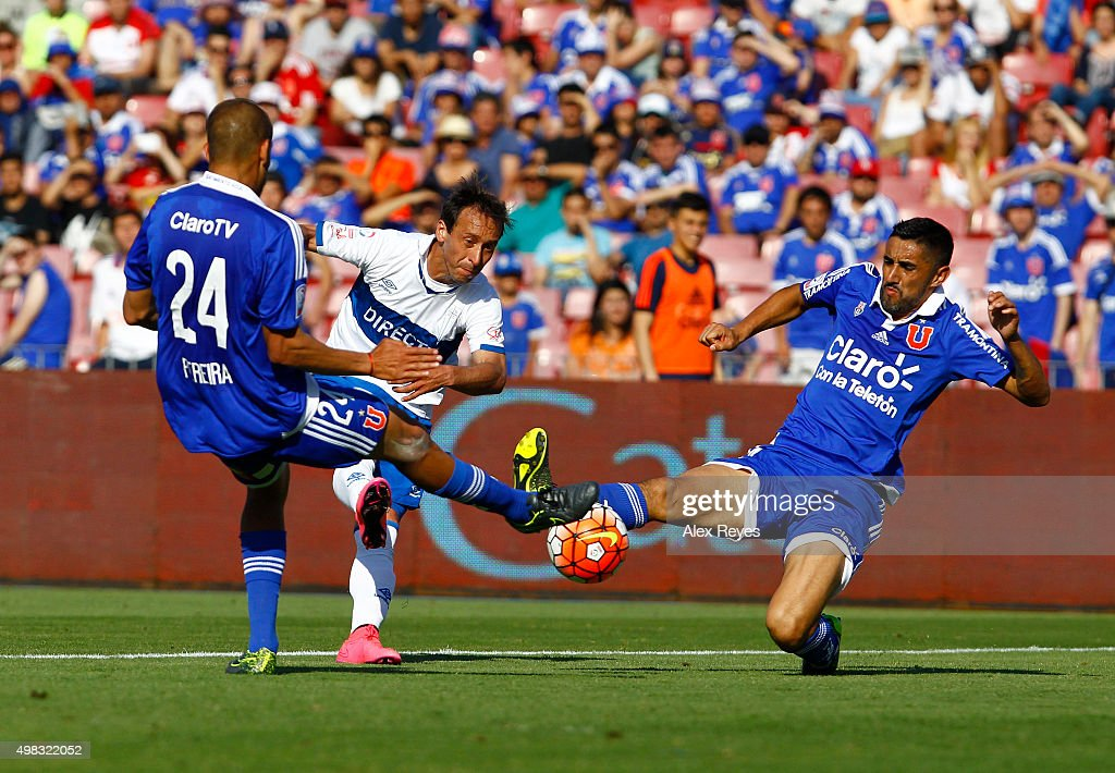 Michael Rios of Universidad Catolica fights for the ball with Osvaldo Gonzalez of U de Chile during a match between U de Chile and Universidad Catolica as part of 13th round of Campeonato Apertura 2015 at Nacional Stadium on November 22, 2015 in Santiago, Chile.
