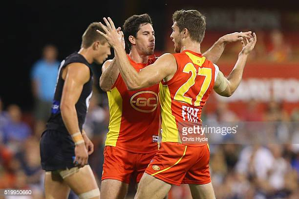 Michael Rischitelli and Clay Cameron of the Suns celebrate a goal during the round three AFL match between the Gold Coast Suns and the Carlton Blues...