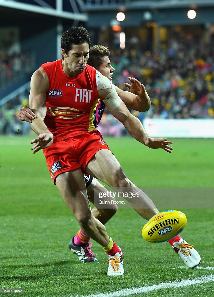 <a gi-track='captionPersonalityLinkClicked' href=/galleries/search?phrase=Michael+Rischitelli&family=editorial&specificpeople=574266 ng-click='$event.stopPropagation()'>Michael Rischitelli</a> of the Suns kicks whilst being tackled by Daniel Howe of the Hawks during the round 14 AFL match between the Hawthorn Hawks and the Gold Coast Suns at Aurora Stadium on June 26, 2016 in Launceston, Australia.