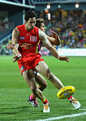 Michael Rischitelli of the Suns kicks whilst being tackled by Daniel Howe of the Hawks during the round 14 AFL match between the Hawthorn Hawks and...