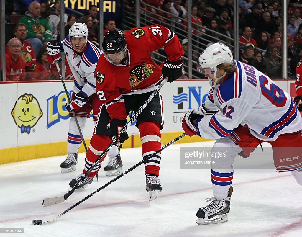 Michael Rozsival #32 of the Chicago Blackhawks moves between <a gi-track='captionPersonalityLinkClicked' href=/galleries/search?phrase=Marc+Staal&family=editorial&specificpeople=3809026 ng-click='$event.stopPropagation()'>Marc Staal</a> #18 (L) and <a gi-track='captionPersonalityLinkClicked' href=/galleries/search?phrase=Carl+Hagelin&family=editorial&specificpeople=4465394 ng-click='$event.stopPropagation()'>Carl Hagelin</a> #62 of the New York Rangers at the United Center on January 8, 2014 in Chicago, Illinois. The Rangers defeated the Blackhawks 3-2.