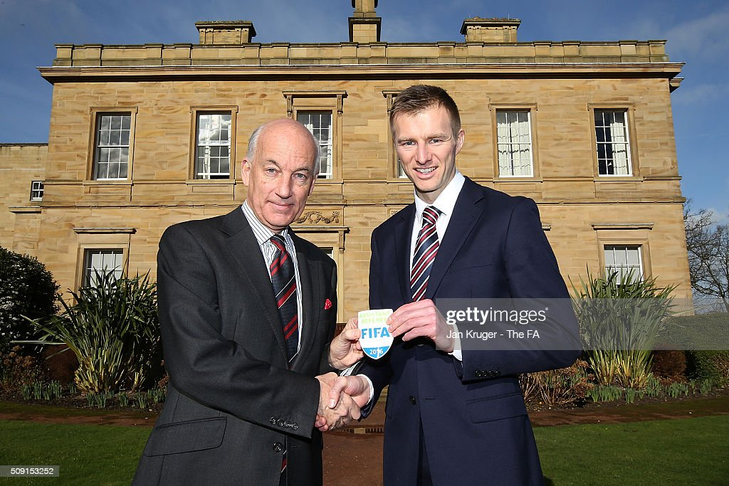 Michael Salisbury (R) receives his FIFA Assistant Referee badge from David Elleray during the FIFA Referees meeting 2016 at Oulton Hall on February 9, 2016 in Leeds, England.
