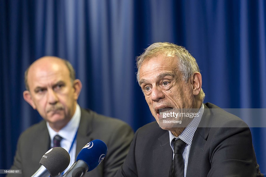 Michael Sarris, Cyprus's finance minister, right, speaks during a news conference following the Eurogroup meeting in Brussels, Belgium, on Monday, March 25, 2013. Cyprus dodged a disorderly default and unprecedented exit from the euro currency by bowing to demands to shrink its banking system in exchange for a 10 billion-euro ($13 billion) bailout. Photographer: Jock Fistick/Bloomberg via Getty Images