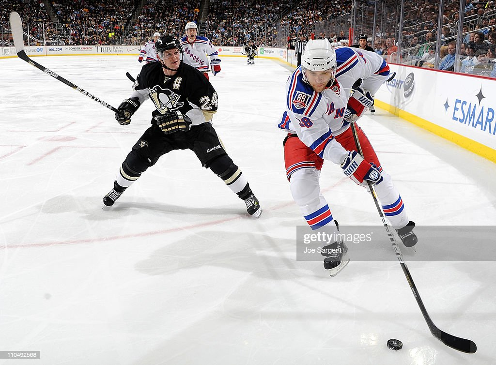 Michael Sauer #38 of the New York Rangers moves the puck in front of the defense of Matt Cooke #24 of the Pittsburgh Penguins on March 20, 2011 at Consol Energy Center in Pittsburgh, Pennsylvania.