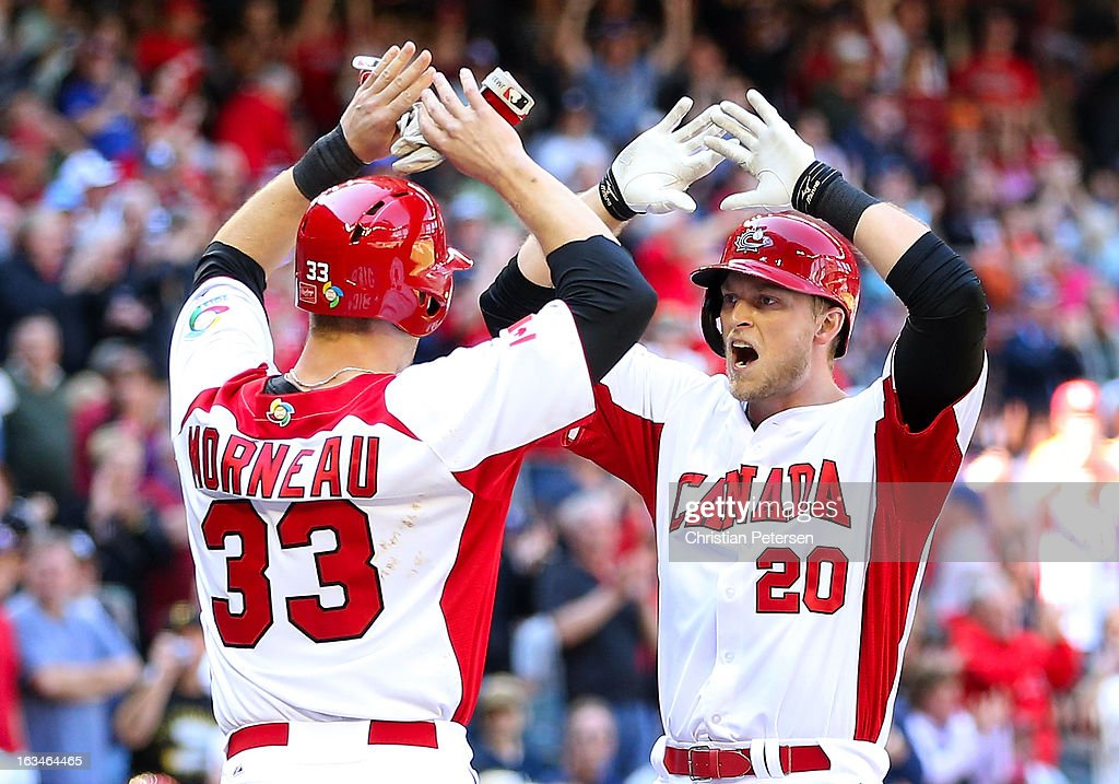Michael Saunders #20 of Canada high fives <a gi-track='captionPersonalityLinkClicked' href=/galleries/search?phrase=Justin+Morneau&family=editorial&specificpeople=211556 ng-click='$event.stopPropagation()'>Justin Morneau</a> #33 after hitting a two run home run against USA during the second inning of the World Baseball Classic First Round Group D game at Chase Field on March 10, 2013 in Phoenix, Arizona.