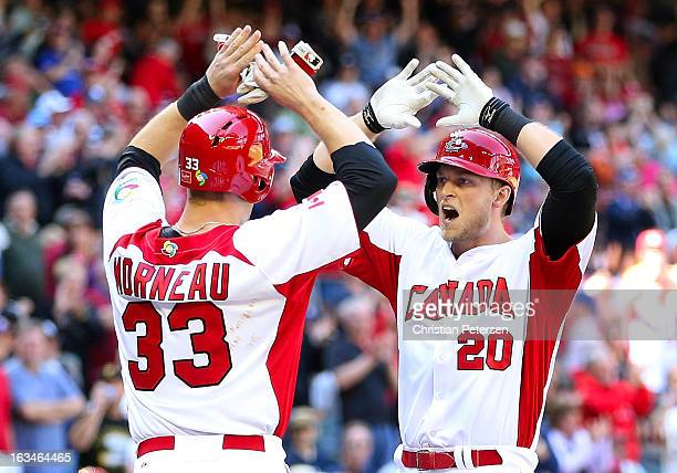 Michael Saunders of Canada highfives Justin Morneau after hitting a tworun home run against USA during the second inning of the World Baseball...