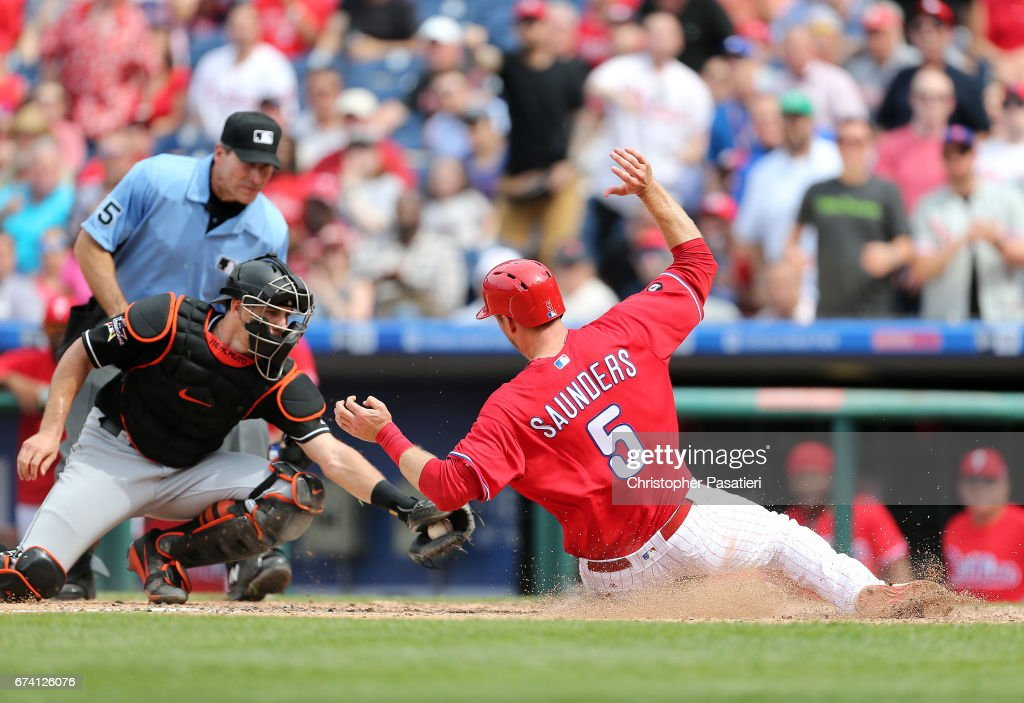 Michael Saunders #5 of the Philadelphia Phillies slides under the tag attempt of J.T. Realmuto #11 of the Miami Marlins to score what would be the game winning run in the bottom to the sixth inning on April 27, 2017 at Citizens Bank Park in Philadelphia, Pennsylvania. The Phillies defeated the Marlins 3-2.