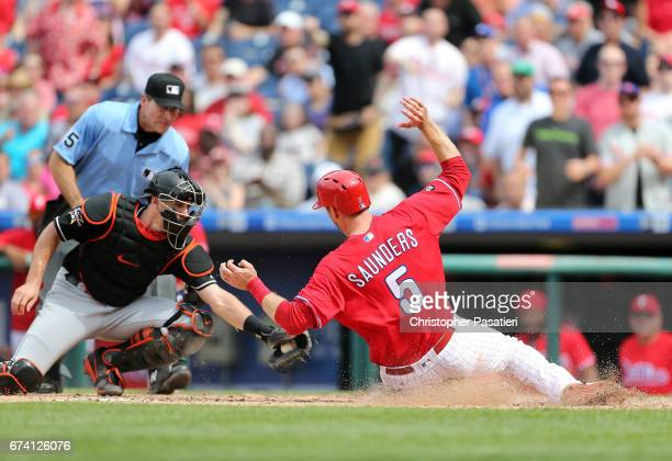 Michael Saunders of the Philadelphia Phillies slides under the tag attempt of JT Realmuto of the Miami Marlins to score what would be the game...