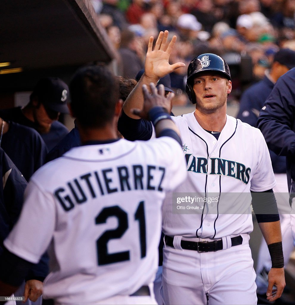 Michael Saunders #55 of the Seattle Mariners is congratulated by <a gi-track='captionPersonalityLinkClicked' href=/galleries/search?phrase=Franklin+Gutierrez&family=editorial&specificpeople=837650 ng-click='$event.stopPropagation()'>Franklin Gutierrez</a> #21 after scoring on a double by Kendrys Morales in the third inning against the Houston Astros on Opening Day at Safeco Field on April 8, 2013 in Seattle, Washington. The Mariners defeated the Astros 3-0.