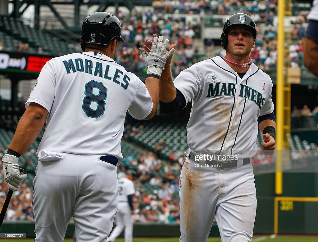 Michael Saunders #55 of the Seattle Mariners is congratulated by Kendrys Morales #8 after scoring on a sacrifice fly by Kyle Seager in the fifth inning against the Oakland Athletics at Safeco Field on May 12, 2013 in Seattle, Washington.
