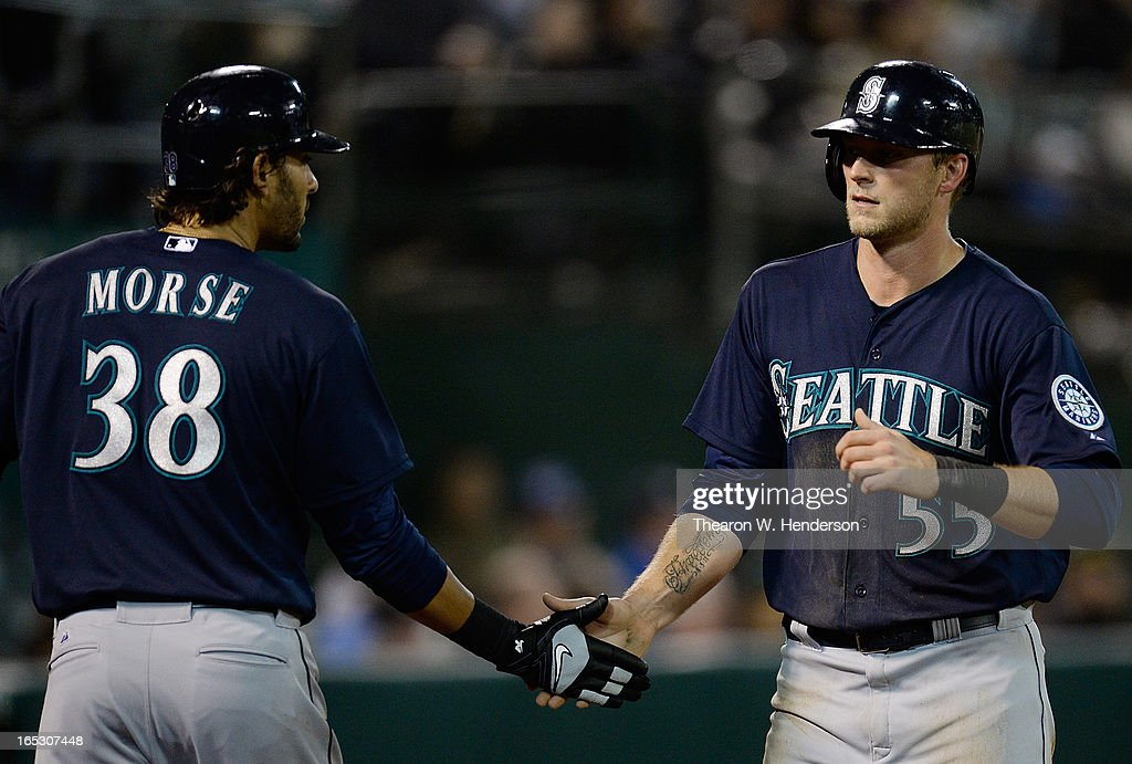 Michael Saunders #55 of the Seattle Mariners is congratulated by Michael Morse #38 after Saunders scored on an RBI double from Kyle Seager #15 (not pictured) against the Oakland Athletics in the eighth inning at O.co Coliseum on April 2, 2013 in Oakland, California. The Mariners won the game 7-1.