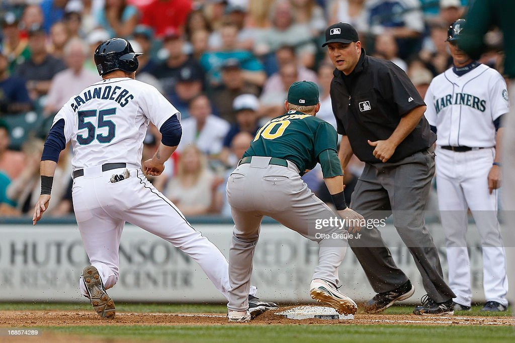 Michael Saunders #55 of the Seattle Mariners is tagged out by first baseman <a gi-track='captionPersonalityLinkClicked' href=/galleries/search?phrase=Daric+Barton&family=editorial&specificpeople=682626 ng-click='$event.stopPropagation()'>Daric Barton</a> #10 of the Oakland Athletics on a pick-off throw from catcher Derek Norris as umpire Dan Bellino #2 makes the call in the fourth inning at Safeco Field on May 11, 2013 in Seattle, Washington.