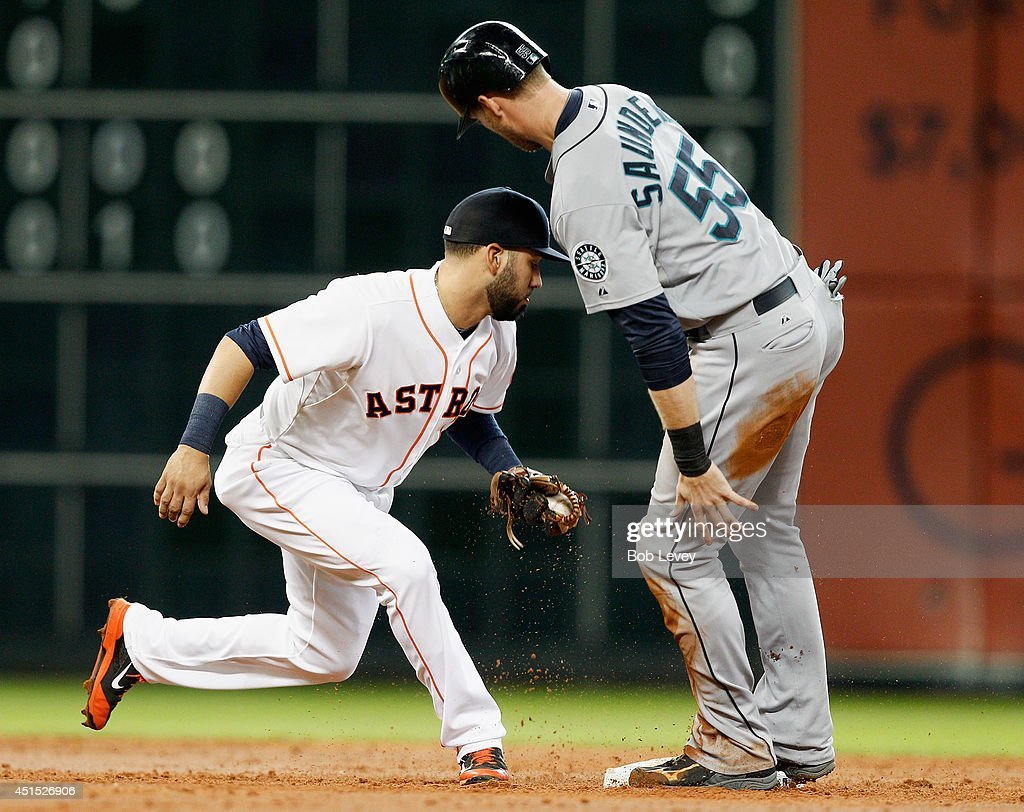 Michael Saunders #55 of the Seattle Mariners is tagged out by Marwin Gonzalez #9 of the Houston Astros at Minute Maid Park on June 30, 2014 in Houston, Texas.