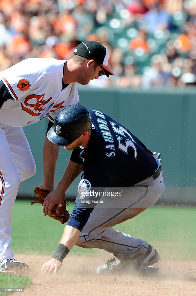 Michael Saunders #55 of the Seattle Mariners is tagged out trying to steal second base in the seventh inning by <a gi-track='captionPersonalityLinkClicked' href=/galleries/search?phrase=J.J.+Hardy&family=editorial&specificpeople=216446 ng-click='$event.stopPropagation()'>J.J. Hardy</a> #2 of the Baltimore Orioles at Oriole Park at Camden Yards on August 4, 2013 in Baltimore, Maryland.