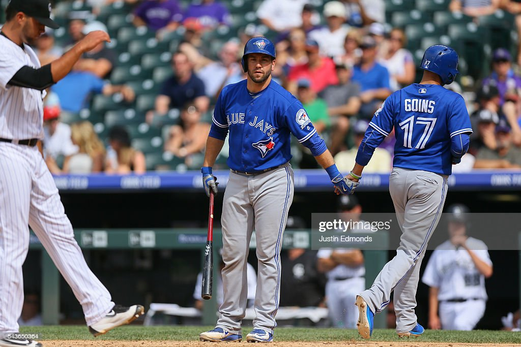 <a gi-track='captionPersonalityLinkClicked' href=/galleries/search?phrase=Michael+Saunders+-+Baseball+Player&family=editorial&specificpeople=10553013 ng-click='$event.stopPropagation()'>Michael Saunders</a> #21 of the Toronto Blue Jays congratulates <a gi-track='captionPersonalityLinkClicked' href=/galleries/search?phrase=Ryan+Goins&family=editorial&specificpeople=9004043 ng-click='$event.stopPropagation()'>Ryan Goins</a> #17 after after he scored on a wild pitch by Carlos Esteves (L) #54 of the Colorado Rockies during the ninth inning at Coors Field on June 29, 2016 in Denver, Colorado. The Blue Jays defeated the Rockies 5-3.