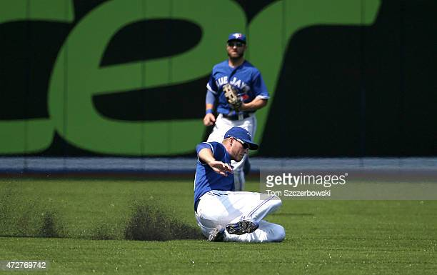 Michael Saunders of the Toronto Blue Jays makes a defensive play to end the third inning as Kevin Pillar watches during MLB game action against the...