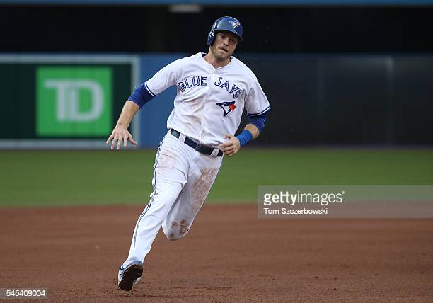 Michael Saunders of the Toronto Blue Jays scores from first base on an RBI double by Russell Martin in the first inning during MLB game action...