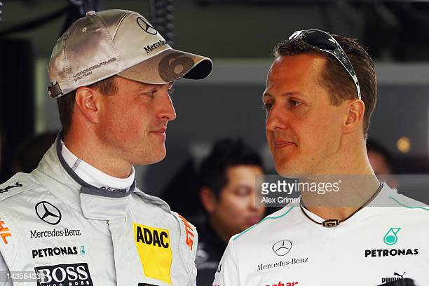 Michael Schumacher and his brother Ralf chat prior to the first race of the DTM German Touring Car Championship at Hockenheimring on April 29 2012 in...