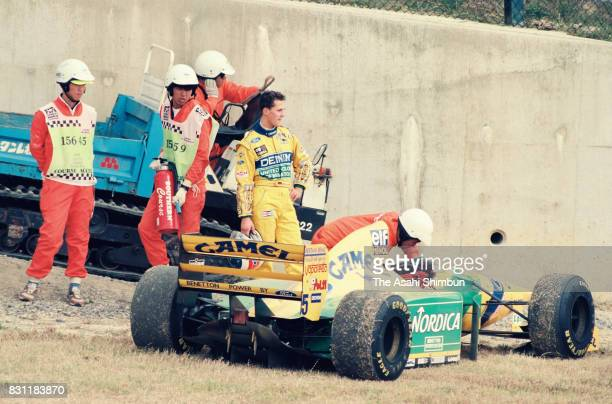 Michael Schumacher of Germany and BenettonFord stands by his machine after retiring during the Formula One Japanese Grand Prix at Suzuka Circuit on...