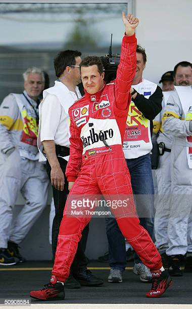 Michael Schumacher of Germany and Ferrari celebrates in the pitlane after securing pole position during the qualifying session for the European F1...