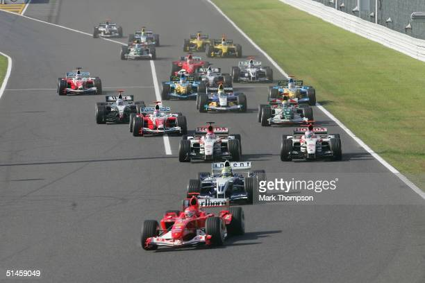 Michael Schumacher of Germany and Ferrari leads into the first corner at the start of the Formula One Japanese Grand Prix at Suzuka Circuit on...