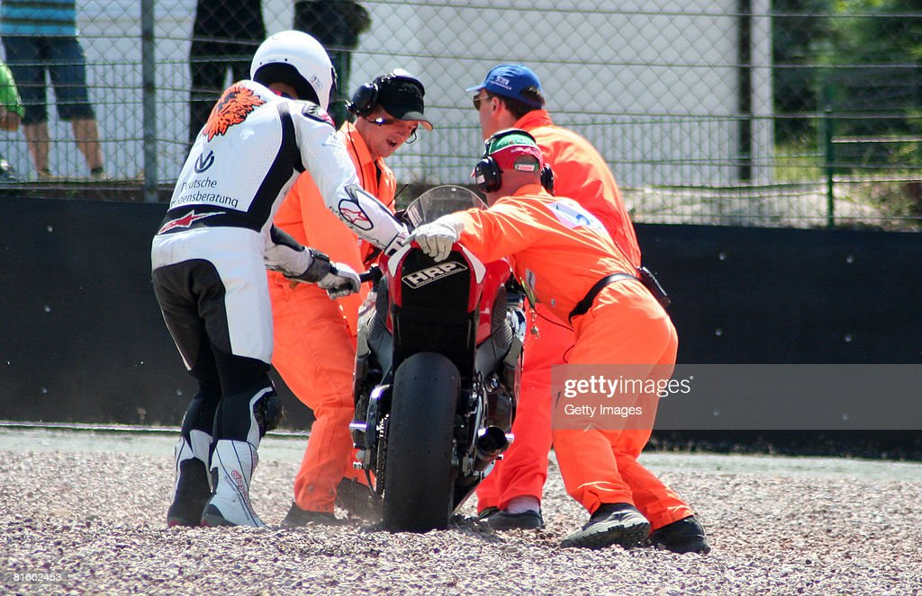 Michael Schumacher of Germany and mechanics push the bike of Schumacher after a crash during the race of the international German motorbike...