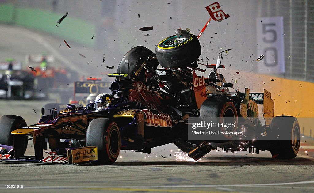 <a gi-track='captionPersonalityLinkClicked' href=/galleries/search?phrase=Michael+Schumacher&family=editorial&specificpeople=157602 ng-click='$event.stopPropagation()'>Michael Schumacher</a> (R) of Germany and Mercedes GP crashes with <a gi-track='captionPersonalityLinkClicked' href=/galleries/search?phrase=Jean-Eric+Vergne&family=editorial&specificpeople=7077576 ng-click='$event.stopPropagation()'>Jean-Eric Vergne</a> of France and Scuderia Toro Rosso during the Formula One Grand Prix of Singapore at Marina Bay Street Circuit on September 23, 2012 in Singapore.