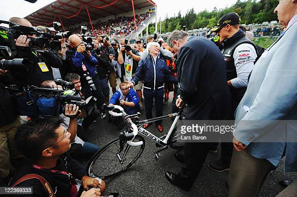 Michael Schumacher of Germany and Mercedes GP is presented with a road bike by cycling legend Eddy Merckx as he celebrates the 20th anniversary of...