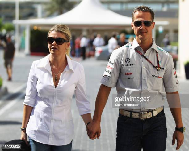 Michael Schumacher of Germany and Mercedes GP walks with his wife Corrina in the paddock during previews to the Abu Dhabi Formula One Grand Prix at...