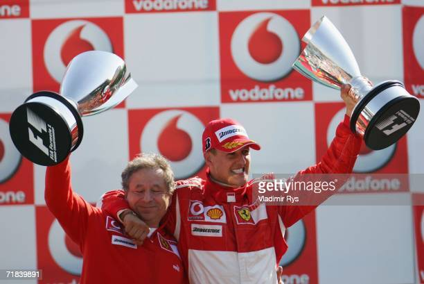 Michael Schumacher of Germany and team principal Jean Todt of Ferrari celebrate during the medal ceremony after winning the Italian Formula One Grand...