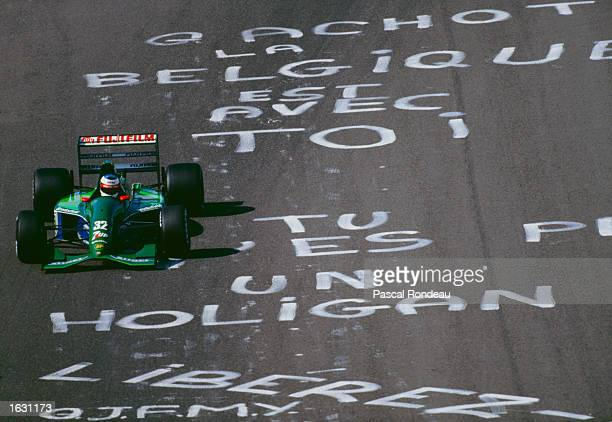 Michael Schumacher of Germany drives past graffiti protesting at the exclusion of Bertrand Gachot of Belgium in the Jordan Team before the Belgian...