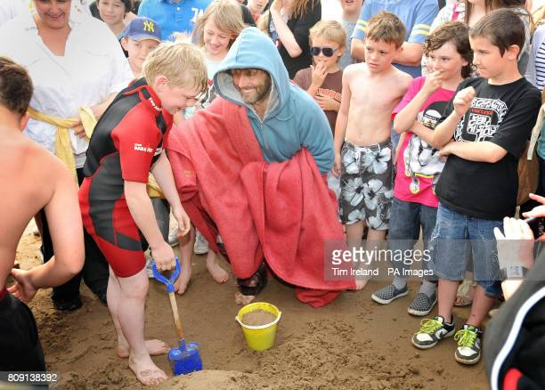 Michael Sheen on Port Talbot beach helps a boy with his sand castle while starring in a oneoff play called 'The Passion' which started today and will...