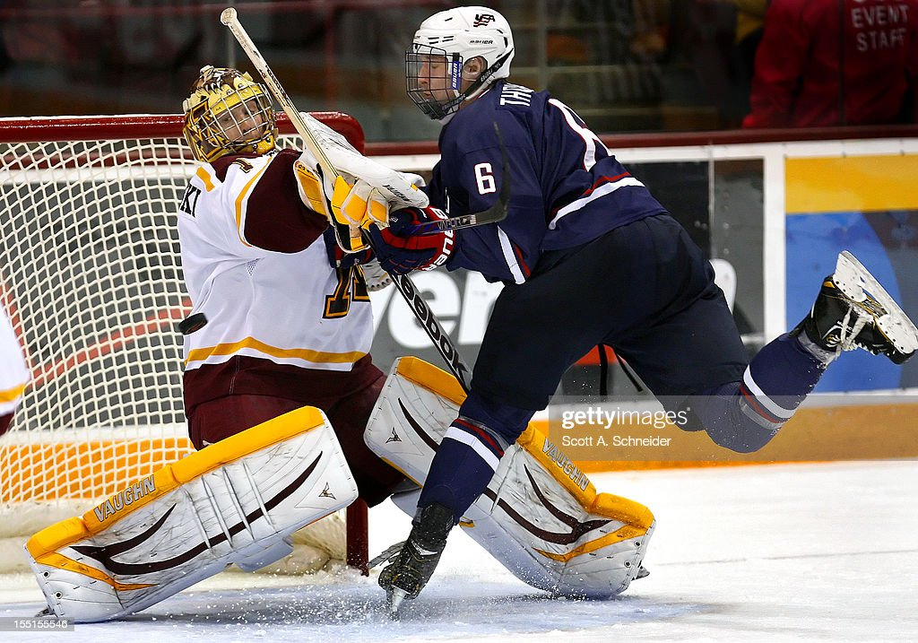Michael Shibrowski #1 of the University of Minnesota makes a save and is hit by Keaton Thompson #6 of the United States U-18 team October 26, 2012 at Mariucci Arena in Minneapolis, Minnesota.