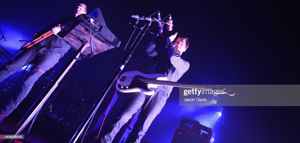 Michael Shuman of Queens of the Stone Age leads the crowd in song during a performance at Nashville Municipal Auditorium on October 7, 2013 in Nashville, Tennessee.