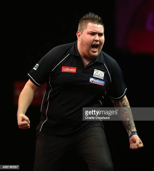 Michael Smith of England celebrates after winning his second round match against Phil Taylor of England during the Ladbrokescom World Darts...