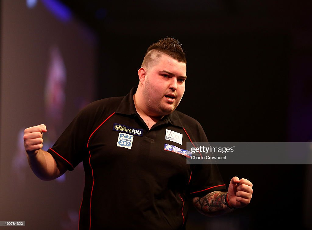 Michael Smith of England celebrates winning his first round match against Mensur Suljovic of Austria during the William Hill PDC World Darts...
