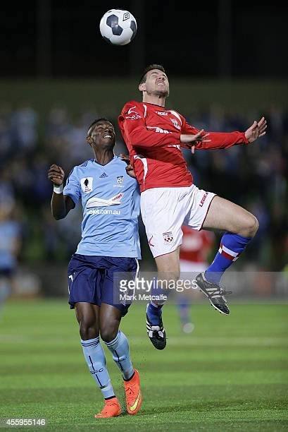 Michael Stamatellis of United heads the ball under the challenge of Bernie Ibini of Sydney during the FFA Cup match between Sydney United 58 FC and...