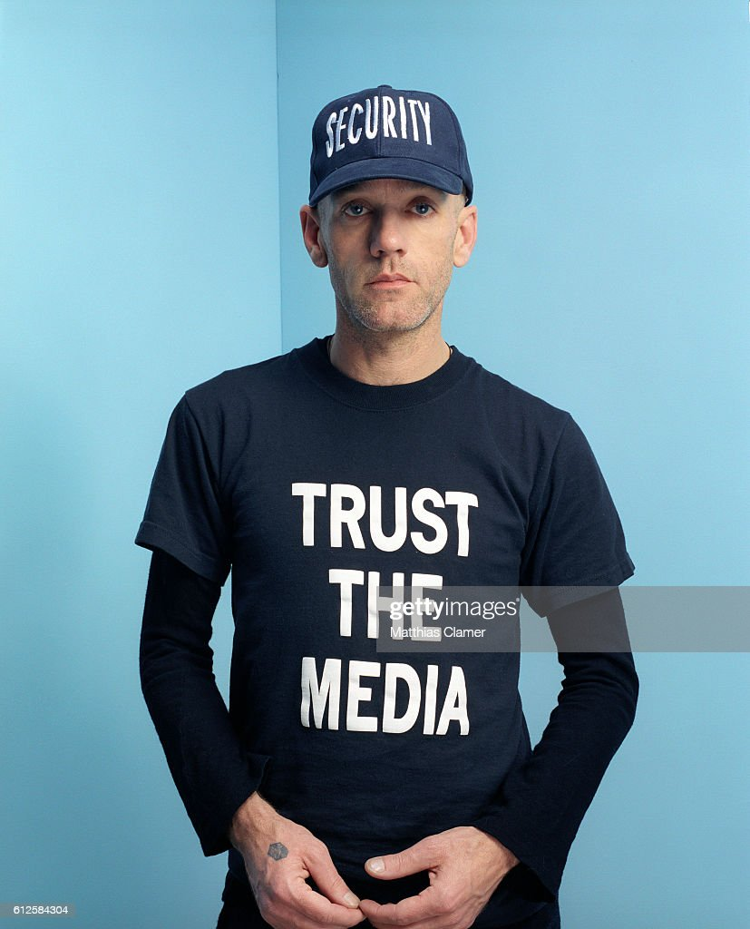 Michael Stipe wears a security cap and a t-shirt that reads, 'Trust the media.'