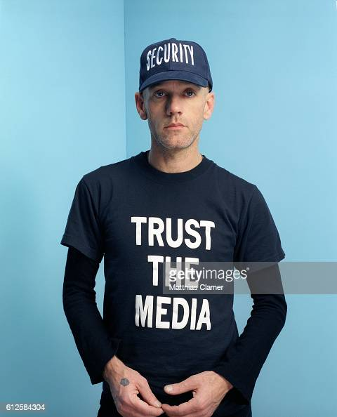 Michael Stipe wears a security cap and a tshirt that reads 'Trust the media'
